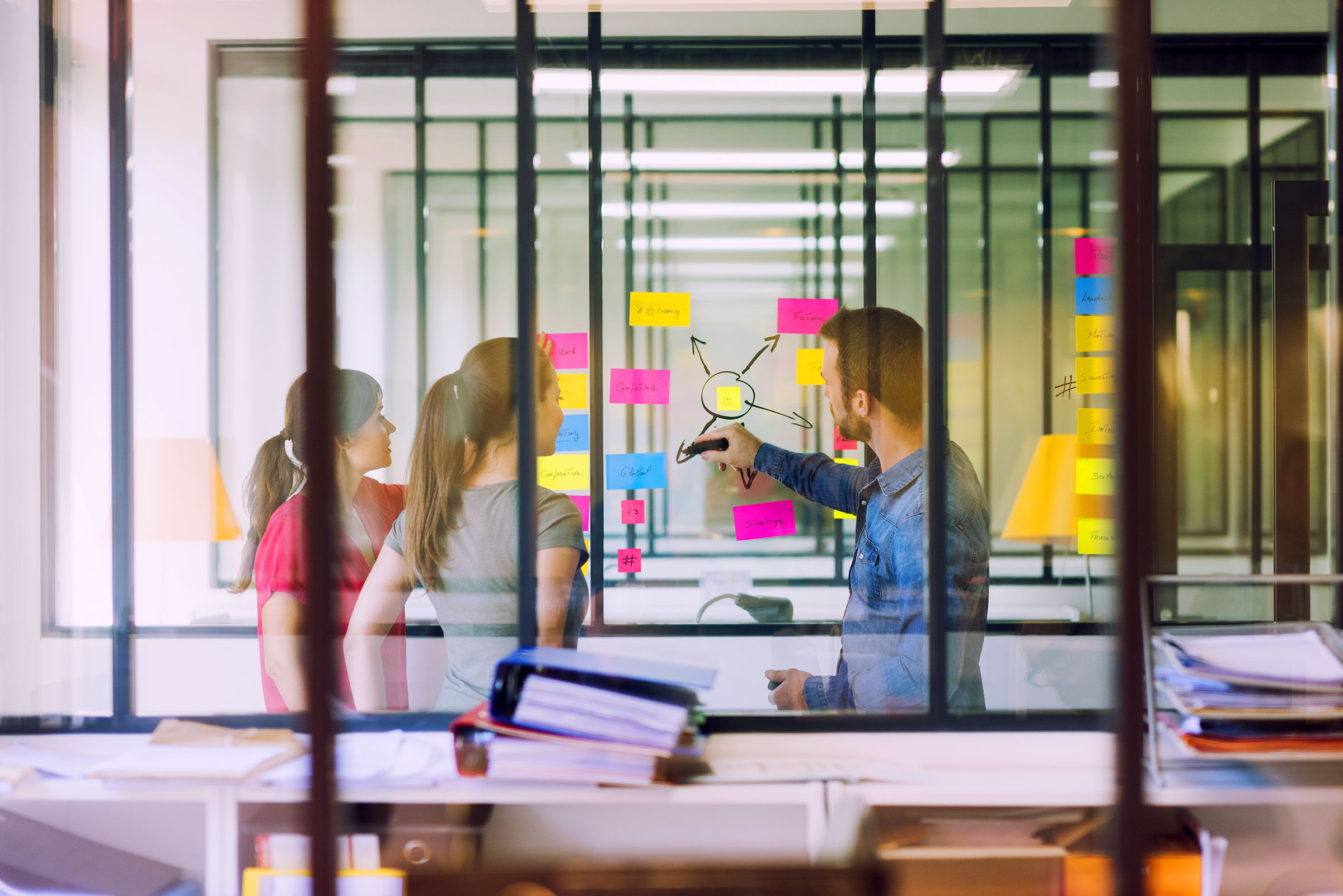 Group-of-business-people-working-in-front-of-glass-wall-with-post-notes