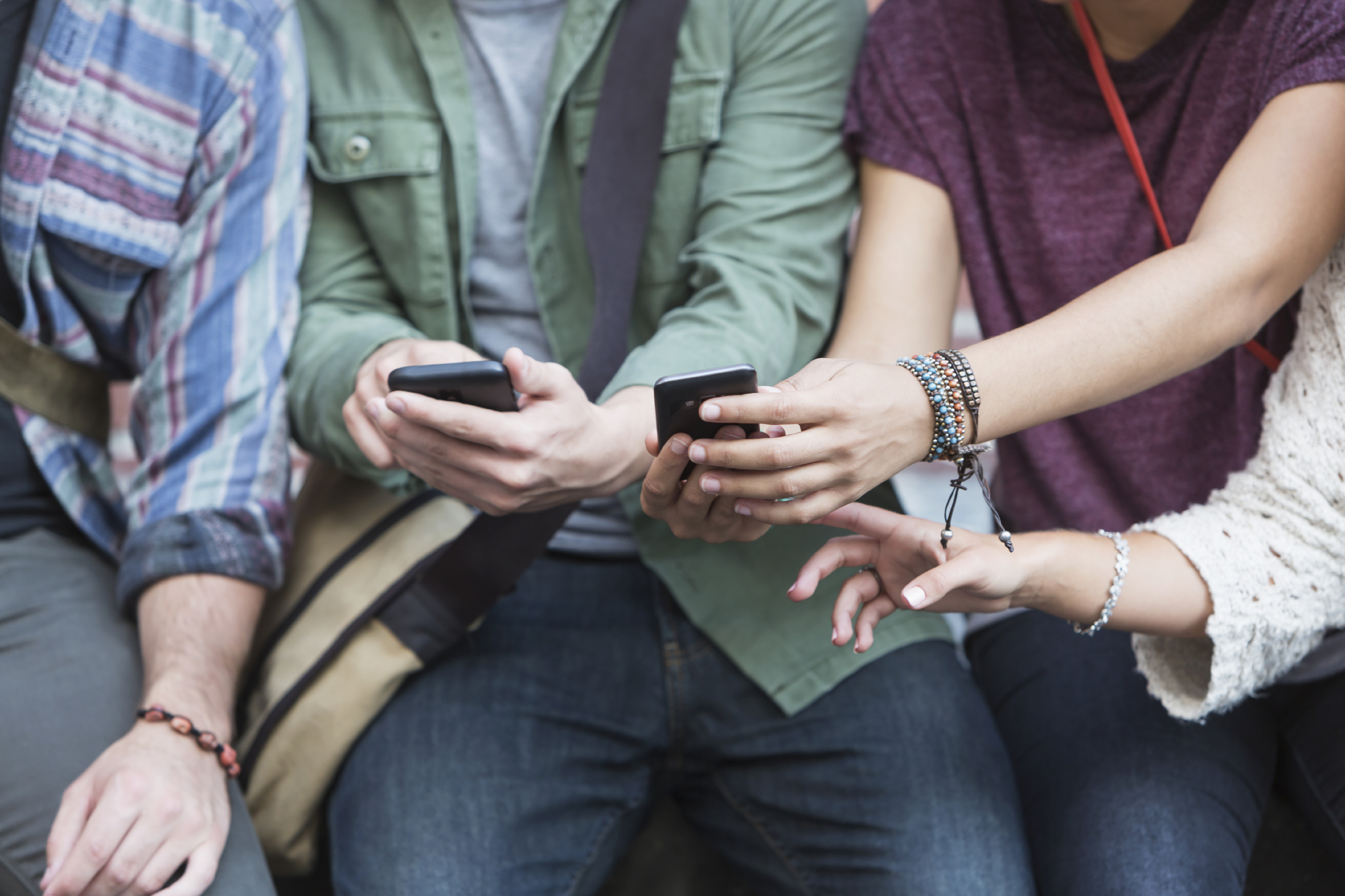 Hands-of-young-adults-with-mobile-phones