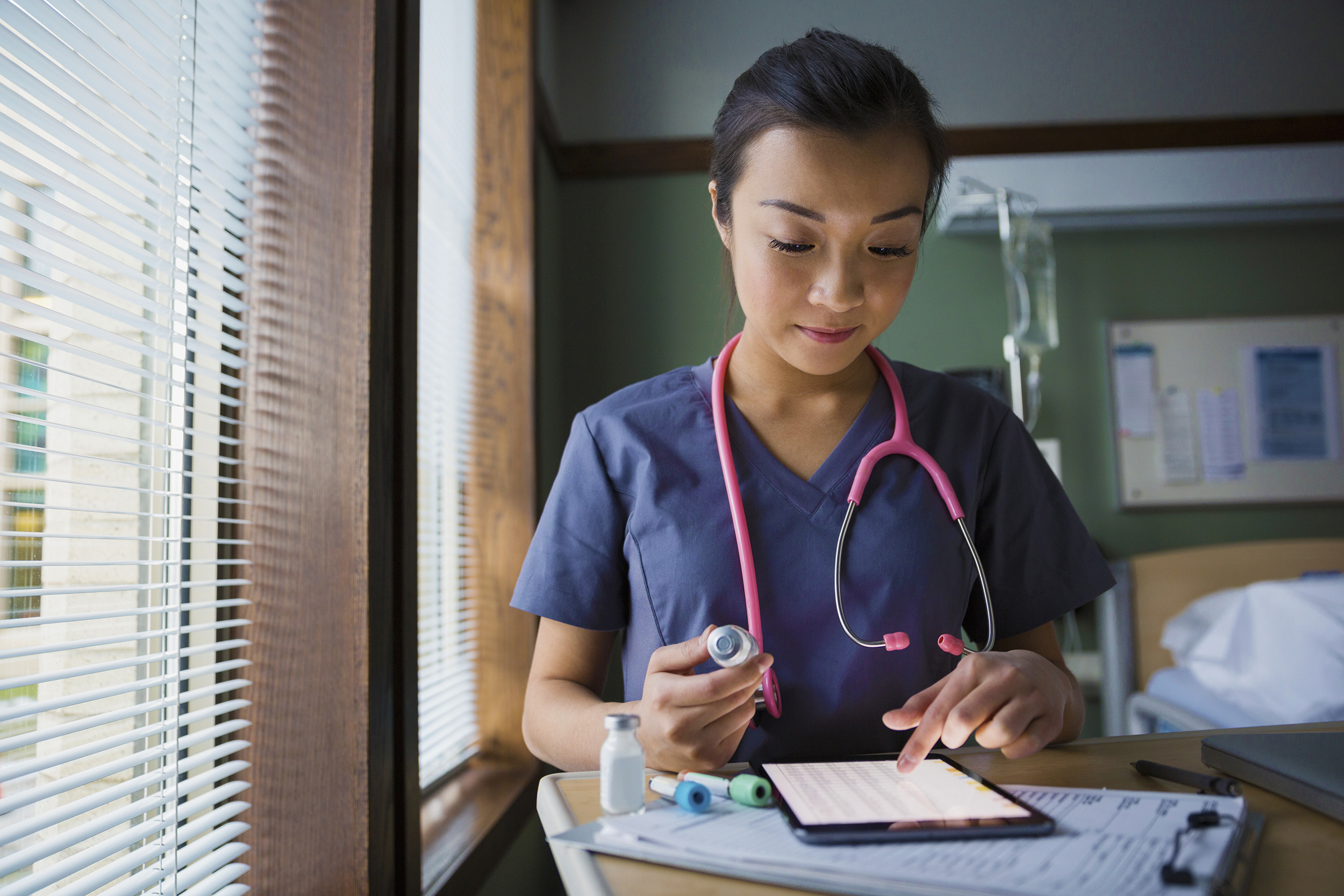 Nurse-using-digital-tablet-in-hospital-room
